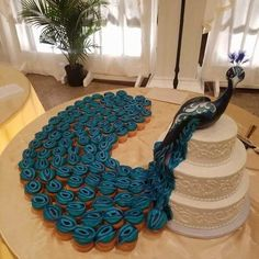 Awesome Peacock Cake -  Looks like a roll of layers of fondant sliced for feathers, on simple iced cupcakes.  Bird - decoration or made of fondant?  Could even display with a fake layered cake and just have the cupcakes.