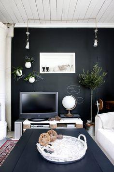 Musta televisio maastoutuu mustalla liitutaulu-maalilla maalattuun seinään. Kasvien latinalaiset nimet ja puhekuplat ovat hauskoja yksityiskohtia. Vanhasta ovi-aukosta on jäljellä vain muisto hylly-syvennyksenä. Valaisimet Ikeasta ja pöytä Kodin Ykkösestä.
