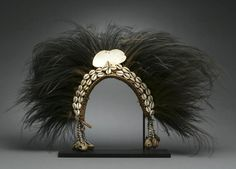 Papua New Guinea   New Guinea headdress of classical form, with cowrie shell headband, a large ovoid shell apex, and strings of seeds and shells to either side; the whole crowned with a dense spread of black cassowary feathers   Est. 2,500 - 3,500$