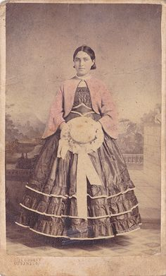 Lovely young lady. Zouave style jacket over what looks like a yoked boat neck bodice. Medici belt and lovely hat. With her skirts being short, she is either right at 16, but likely younger.