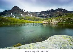 Download this stock image: Lights and cloudy sky on lake Nivolet.  The Gran Paradiso National Park, Aosta Valley, Italy. - F6XG9A from Alamy's library of millions of high resolution stock photos, illustrations and vectors.