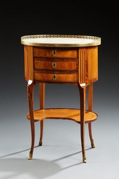 Coffee table oval veneer rosewood inlaid leaves in frames threaded jagged on land against rosewood.  It opens with three drawers. Amounts dishes triple wall. Arched feet Shelf Kidney shape.  Transition periods of Louis XV and Louis XVI.