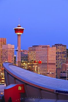 Picture of the Saddledome standing before the Calgary Tower, Calgary skyline at sunrise  Canada