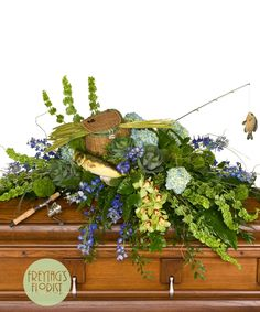 Fisherman is a creative casket spray that includes flowers and objects personalized to represent fishing activities. Fishing rod and tackle box must be supplied. Freytag's Florist can supply for an additional cost. Casket Flowers, Grave Flowers, Funeral Flowers, Cemetery Flowers, Funeral Floral Arrangements, Flower Arrangements, Table Arrangements, Funeral Sprays, Casket Sprays