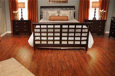 Master bedroom with orange accents. Hardwood floors.