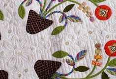 Laurel Keith machine-quilted a flower-and-vine motif across the intersections of the appliqued blocks.