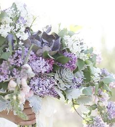 A loose asymmetrical bouquet of green viburnum, lavender lilacs, pale green succulents, purple succulents, fresh lavender, spirea, silver dollar eucalyptus, jasmine vine, nagi, lavender sweet peas, and white clematis vine wrapped in ivory ribbon with the stems showing