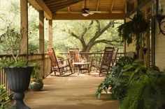 this is porch is wider, I like that and the green plants and rocking chairs!