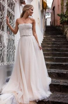 Salome is a stunning two piece wedding gown. Stunning detailed, structured bodice with gorgeous lace. The layered tulle skirt is covered in beautiful pearls and features a gorgeous beaded waist band. This stunning Galina Couture two piece is exclusively available at Luella's Bridal
