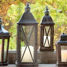 "Wood lantern base with a weathered stain crowned by a metal top and chimney. Statuesque set sporting a decorative ""X"" lattice on the sides. Medium is 22 inches high; large is 31 inches high. brbr..."