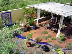 Pictures of Mediterranean-Style Gardens and Landscapes: The blue-rock faux stream makes a low-maintenance water feature. But there isnt a lack of water, the mosaic tile on the wall sits atop a small fountain. The freeform terra cotta patio interspersed with moss and groundcover give this gathering spot lovely Old World charm. Design by Katrina Fairchild.  From DIYnetwork.com