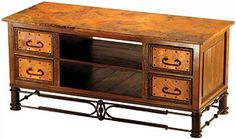 The Copper Collection Grande coffee table sits on an elegant iron stand and features four long drawers and two cubby holes.  The hand-hammered copper top will look great in your living room! This tall piece can also double as a Plasma/LCD entertainment stand.