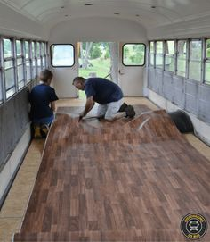 Laying out linoleum flooring in school bus
