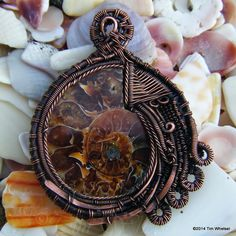 This handmade wire wrap pendant was wrapped with pure copper wire that flows beautifully around the ammonite fossil. The copper was then antiqued to give a nice rustic steampunk look.