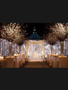 love the idea of tall branched flower vases perched atop columns lining the faux aisle, paving an elegant path to the stage - white floral mandap, white mandap wedding decor by Tantawan Bloom #indianwedding #weddingTantawan Bloom