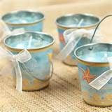 Create beach-inspired luminaries to serve as table centerpieces. Prepare a luminary for each table by filling a plastic or tin beach bucket (without handles) about three-fourths full of play sand. Place a narrow candle in the center of each bucket so that the candle is safely embedded in the play sand