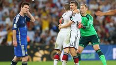 RIO DE JANEIRO, BRAZIL - JULY 13: Thomas Mueller, Bastian Schweinsteiger and Manuel Neuer of Germany celebrate the win while Lionel Messi of Argentina shows his dejection after the 2014 FIFA World Cup Brazil Final match between Germany and Argentina at Maracana on July 13, 2014 in Rio de Janeiro, Brazil. (Photo by Alex Livesey - FIFA/FIFA via Getty Images)