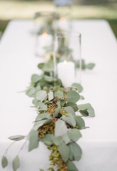 Centerpieces featuring seeded eucalyptus garlands and white candles // Sean Money + Elizabeth Fay