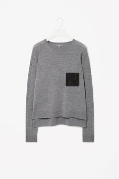 This jumper is made from finely knitted merino wool and has a leather patch pocket on the chest for a modern contrast of textures. A loose, relaxed fit with dropped shoulders seams, it has a graduated hem, long raglan sleeves and a classic round neckline.