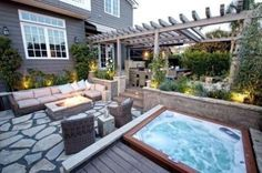 a square jacuzzi with a wooden deck next to an outdoor living room