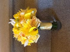 Bright and monochromatic bouquet of yellow spider mums, roses, freesia, iris, and mini calla lilies.