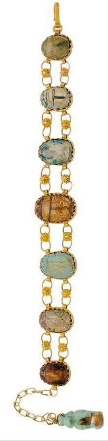 [Bracelet] An Antique Egyptian Revival Suite, circa 1906  Including a necklace composed of a fine trace linking chain suspending a series of hardstone scarabs, eight gold charms with two decorated by polychrome enamel, length 19 1/2 ins, together with Ralph H. Blanchard receipt; and a bracelet alternating hardstone scarabs between twin floral links, length 6 1/2 ins, with fitted box