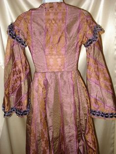 "late 1850s brocade silk dress; trim of purple velvet & fringe; interior sleeves are netted lace and strip of velvet for tightening; hem has deep lining; bust: 30""; waist: 21""; length: 57"""