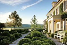 Planted with boxwood clipped to resemble clouds, a sculptural parterre fronts a Dutchess County, New York, farmhouse created by G. P. Schafer Architect; the benches are by Jamb   archdigest.com