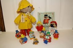"""lot of  10 Paddington plush, figurines & book. #1-plush bear with rain coat, boots, hat, and tag 14"""" from 1981 MINT #2-Paddington at the tower hard cover book #3-Plush in white bag FAO Schwartz #4-figurine Enesco #5-figurine holding letter for Aunt Lucy #6-figurine holding apple #7-'Fresh eggs' in open suitcase figurine #8-plush no bag #9-pushing wagon #10-Stocking holder  #11-mini plastic with fur cover doll/figurine $50"""