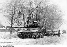 Russia, 22 December 1943. A Mark VI Tiger tank with it's tracks blown off in the snow, parked behind it a Kubelwagen