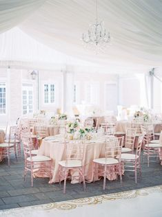 blush reception chairs and white fabric tent with chandelier |