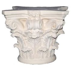 """Table base with Corinthian-style detailing and an antiqued finish.  Product: Table baseConstruction Material: Resin and stone blendColor: LimestoneFeatures: Handmade in the USADimensions: Small: 13"""" H x 15"""" W x 15"""" DMedium: 19"""" H x 21"""" W x 21"""" DLarge: 30"""" H x 24"""" W x 24"""" D"""