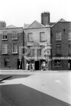Shops on Marrowbone Lane and Thomas Court Bawn, Dublin city, in 1952 or 1953. The dairy M Russell is at number 1 Marrowbone Lane; next door to it at number 1 Thomas Court Bawn is newsagent J Egan. Collection RTÉ Johnson Collection Photographer Johnson, Nevill