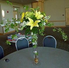 arrangement featuring yellow lily's, yellow and green poms, and white aster.