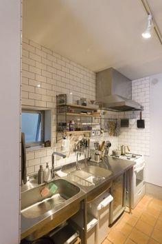 白いタイルにステンレスのシンクがインダストリアルなムードのキッチン。オープンシェルフは後から取り付けた。