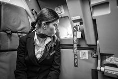 """Flight attendant looking out of a door on a Airbus 320 with a label """"remove before flight""""attached."""