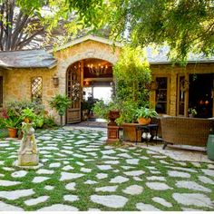 house exterior with rustic stone-clad entry, iron urns, terra-cotta pedestals