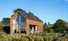 This New Zealand bach (a simple vacation home) has a 592 sq ft main level plus two attic loft bedrooms. Shed Design, Small House Design, Design Case, Modern House Design, Attic Design, Modern Tiny House, Modern Barn, Modern Homes, Modern Garage