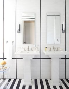 russell groves's black and white bathroom with black and white striped tile floor, two pedestal sinks and long mirror with white paneled wal...