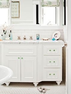 To warm up this all-white guest bathroom, the vintage-look vanity was outifitted with green glass knobs and a glamorous marble countertop. A handful of other vintage-inspired details -- such as the traditional claw-foot tub and the thick grout lines between tiles -- give the bathroom undeniable character.