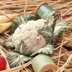Nature's Bounty by Julie Kniedl, Cauliflower pin cushion made of quilted leaves with the center covered in french knots embroidery.