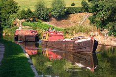 "Historic working narrowboats on the Macclesfield Canal in Cheshire, England. The motor boat at the front ""Forget Me Not"" is pulling along an unpowered butty ""Lilith"". This was the traditional working style used on working boats after motor boats became common."