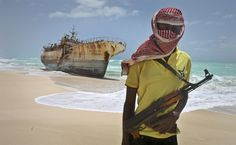 """Somali pirate Hassan stands near a Taiwanese fishing vessel that washed up on shore after pirates were paid a ransom and released the crew, in the once-bustling pirate den of Hobyo, Somalia. """"There's nothing to do here these days. The hopes for a revitalized market are not high,"""" said Hassan, a high school graduate who taught English in private school before turning to piracy in 2009."""