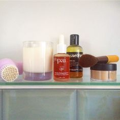 Shelf shot featuring a cleansing brush, homemade soy candle, @paiskincare…