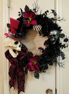 This Dapper looking fellow is all dressed up with his top hat ready to greet your ghosts and goblins. Made from a grapevine wreath, there are plenty of black roses with a touch of dark burgundy added, This not to scary skull is dressed in a top hat with black feathers and a beautiful black and dark burgundy burnt out ribbon. his boney hands are reaching out to make sure all is roses are just right. He even has a little skull friend hanging around too. This wreath is made on a 18 grapevine…