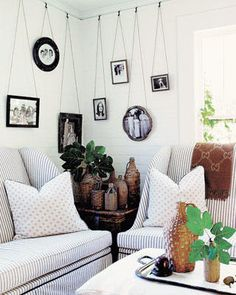 Love the pictures hanging from the picture rail, the striped upholstery and the demijohns - yep, this is my style!