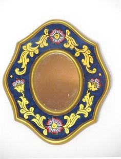 This Peruvian beauty is handmade in glass, wood and gold. Handcrafted with ancient techniques by skilled artisans from the Cajamarca region. Delicate hand painted flowers, leaves and organic shapes decorate this 4 by 3.5 inches mirror. An elegant statement to any bedroom or studio wall.