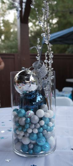 Centerpieces with silver and blue ornaments, crystal stems and silver swirl stems