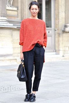 Model Liu Wen's pairs a slouchy sweater with sleek black trousers and a masculine flat.  Image via - ELLE.com
