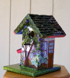This bird house is handcrafted out of pine and hand painted with acrylic paints. The painting is to make the birdhouse look like the house next door, with yard, flowers, trees, etc.    The dimensions of this birdhouse are 4 1/2 wide by 4 1/2 deep by 11 tall. This would be a very good size for sparrows, tree swallows, wrens, and chickadees.    This house is first constructed, then the roof is carved and then we putty nail holes and sand it. Once it has been tacked off we spray it with a clear…